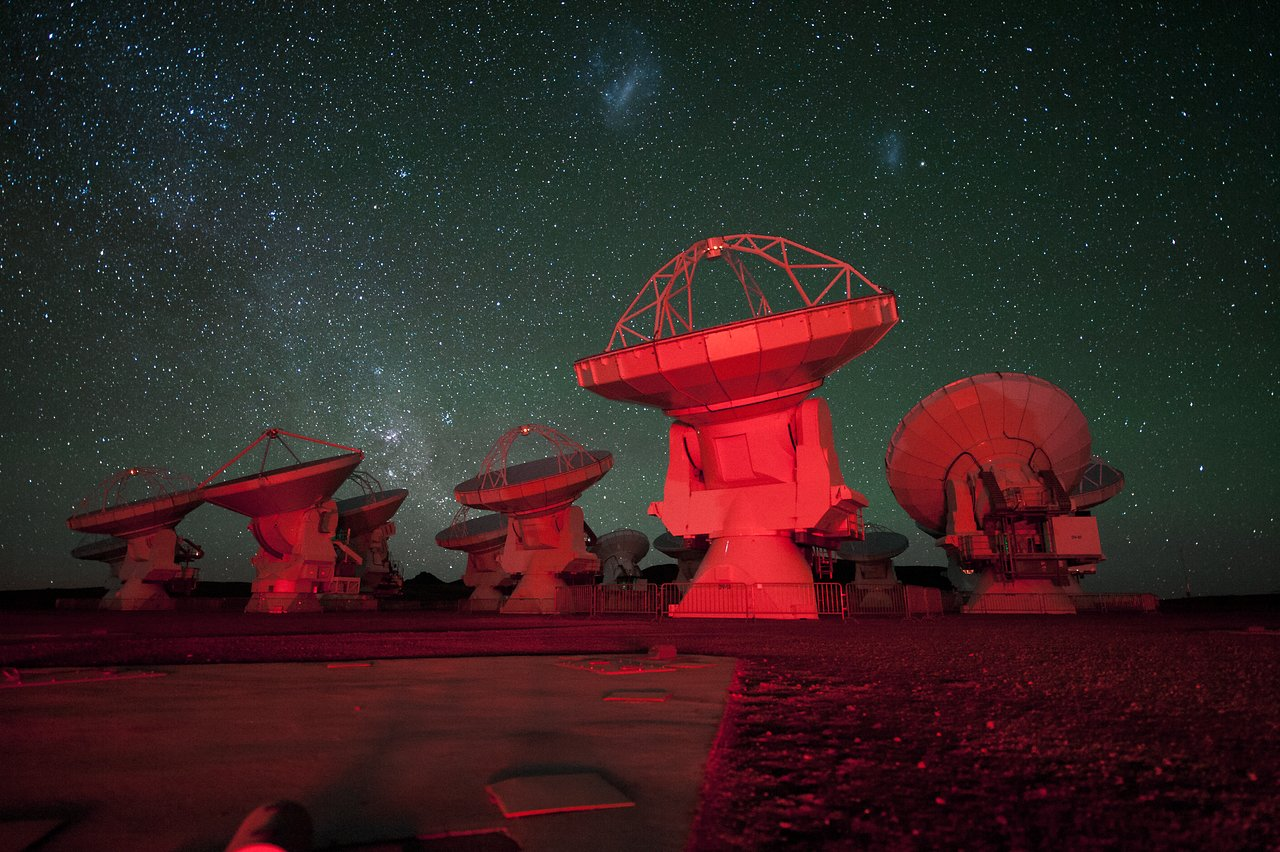 ALMA antennae bathed in red light. in the background there is the southern Milky Way on the left and the Magellanic Clouds at the top. Credit: ESO/C. Malin